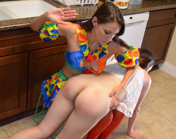 Celeste as a clown gives a spanking - she's not clowning around